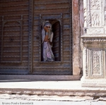 indian woman at the doorway wearing a violet sari watching outside
