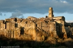 pitigliano sunset view of ancient houses and chirch by red light of sunset