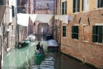 gondola on channel in the ghetto in venice with clothes hung out to dry