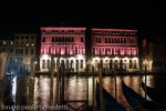 pink facade on channel with gondolas and lights reflections in the night in Venice